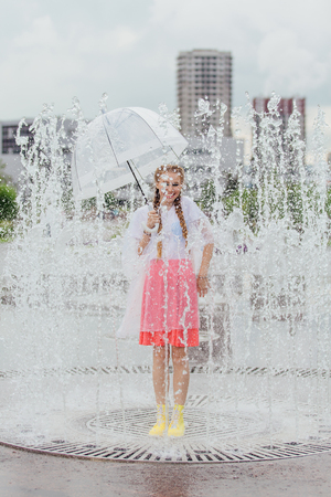 Young wet pretty girl with two braids in yellow boots and with transparent umbrella stands inside of fountain. Rainy day in city.