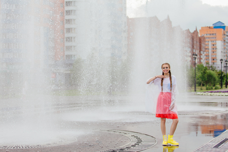Young wet pretty girl with two braids in yellow boots stands near fountain. Rainy day in city. Фото со стока