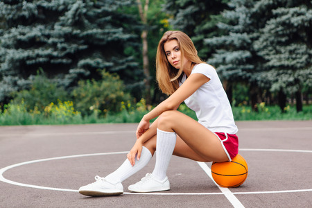 Beautiful young blonde girl dressed in white t-shirt, shorts and sneakers, sits on a basketball court on the ball outdoors. Copy space. Фото со стока