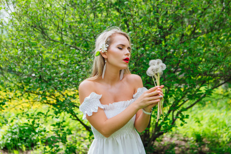 Beautiful blonde woman blowing on white fluffy dandelions blowballs in a green spring park