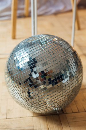 Mirror disco ball laying on the wooden floor Stok Fotoğraf