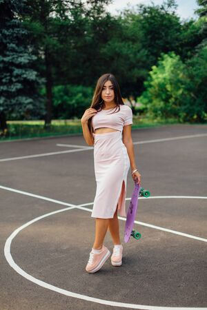 Portrait of a smiling charming brunette female holding in hand her skateboard on a basketball court. Happy woman with trendy look taking break during sunset.