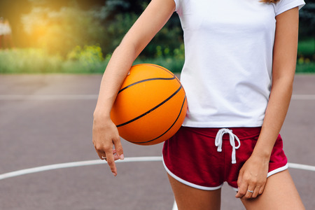 Young woman dressed in white t-shirt, shorts holding a ball on a basketball court outdoors close up. Фото со стока