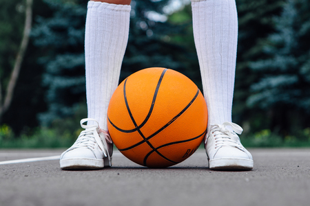 Close up wonans feet in white sneakers and whote long socks, with a ball on a basketball court outdoors.