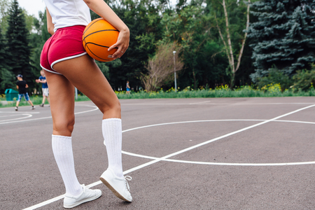 Young woman dressed in white t-shirt, shorts holding a ball on a basketball court outdoors.
