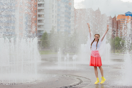 Young wet pretty girl with two braids in yellow boots stands near fountain. Rainy day in city. Banco de Imagens