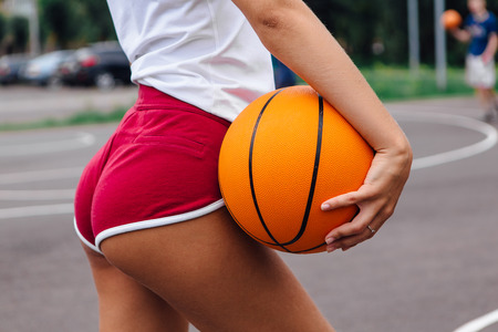 Young woman dressed in white t-shirt, shorts holding a ball on a basketball court outdoors. Close up womans fanny in shorts Фото со стока