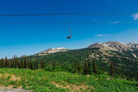 Empty chairs of ski lift at summer time on the background of clear blue sky and green forest Stock Photo
