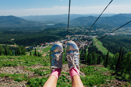 Silver shoes on feet during travel on mountain ski lift at summer time. The view from the mountain elevator