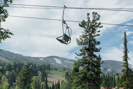 Empty chairs of ski lift at summer time on the background of clear blue sky and green forest Фото со стока