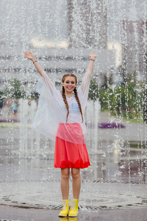 Young wet pretty girl with two braids in yellow boots and with transparent rain clothe stands inside of fountain. Rainy day in city. 免版税图像