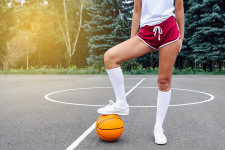 Close up wonans feet in white sneakers and whote long socks, with a ball on a basketball court outdoors. Copy space.