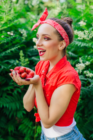 Beautiful young pin up girl dressed in red shirt with bright make up and fresh natural strawberry. Stock Photo