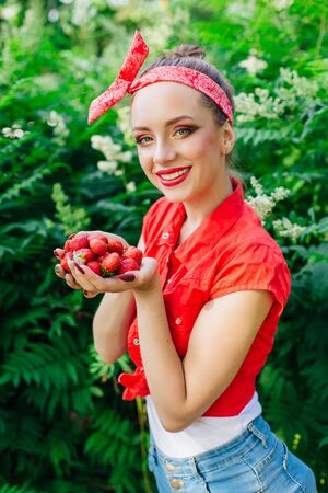 Beautiful young pin up girl dressed in red shirt with bright make up and fresh natural strawberry. Stockfoto