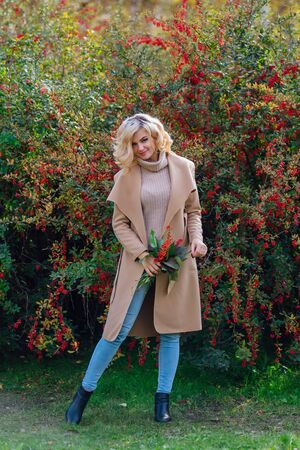 Beautiful elegant blonde woman dressed in a coat standing next barberry bush holding bouquet of rowanberries and leaves in autumn park. Sunny october day. Archivio Fotografico