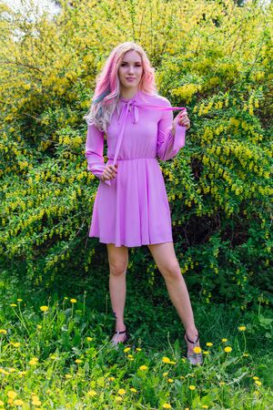 Beautiful fashion model girl with colorful dyed hair and perfect makeup and hairstyle standig next to blooming barberry bush with yellow flowers 版權商用圖片