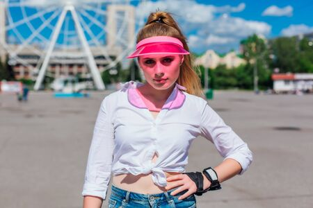 Portrait of an emotional beautiful young girl in a pink cap visor and protective gloves