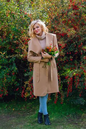 Beautiful elegant blonde woman dressed in a coat standing next barberry bush holding bouquet of rowanberries and leaves in autumn park. Sunny october day.