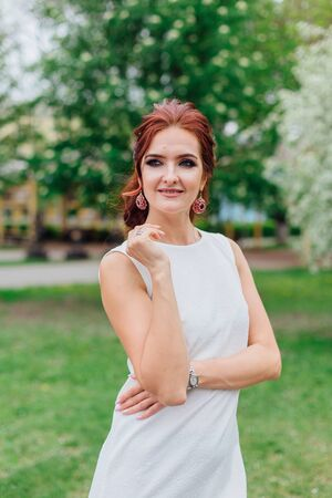 Spring portrait of a charming woman wearing beautiful white dress under the blooming apple tree. Фото со стока