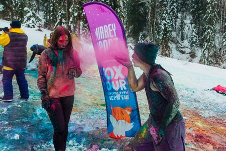Sheregesh, Kemerovo region, Russia - April 06, 2019: Grelka Fest is a sports and entertainment activity for ski and snowboard riders in bikini. Happy young couple painted with holi colors Redactioneel