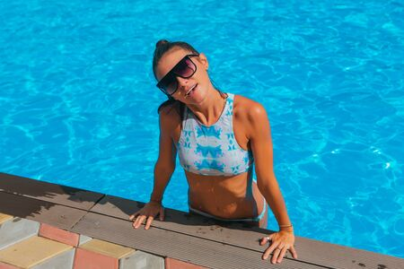 Fashion portrait of beautiful sexy young women in swimming pool outdoors Stockfoto