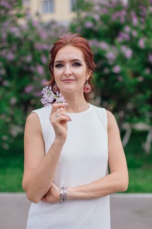 Spring portrait of a charming woman wearing beautiful white dress standing next to blooming purple lilac bush.