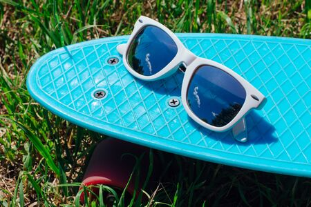 Sunglasses on a blue plastic skateboard penny board with pink wheels stands on the track. Фото со стока
