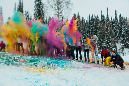 Sheregesh, Kemerovo region, Russia - April 06, 2019: Grelka Fest is a sports and entertainment activity for ski and snowboard riders in bikini. A group of a young people throwing colorful holi powder.