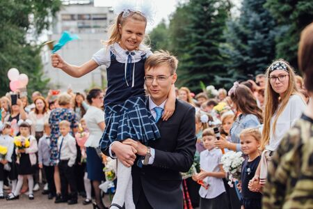 NOVOKUZNETSK, KEMEROVO REGION, RUSSIA - SEP, 1, 2018: Meeting with the first-grade pupils and teacher at schoolyard. The day of knowledge in Russia.
