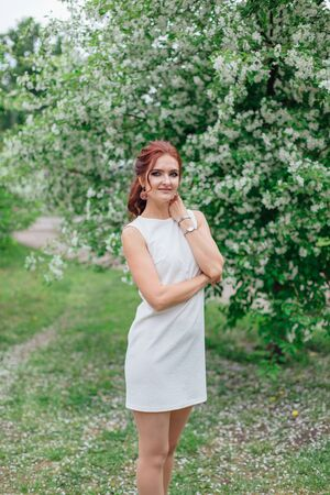Spring portrait of a charming woman wearing beautiful white dress standing under the blooming apple tree.