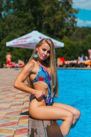 Modeportret van mooie jonge vrouwen die in de buurt van een zwembad met helder blauw water zitten, buiten zonnebaden, voeten in het water zetten Stockfoto