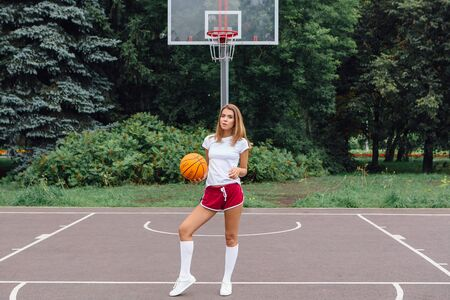 Beautiful young blonde girl dressed in white t-shirt, shorts and sneakers, plays with ball on a basketball court outdoors. Copy space.