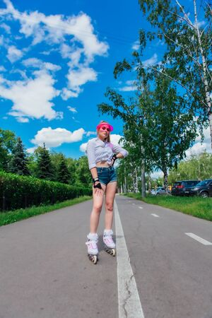 Portrait of an emotional beautiful young girl in a pink cap visor and protective gloves for rollerblades and skateboarding riding on rollerblades on the road. Stockfoto