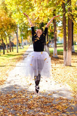 Woman ballerina in a white ballet skirt dancing in pointe shoes in a golden autumn park. Ballerina standing in beautiful ballet pose and teowing up dry yellow leaves