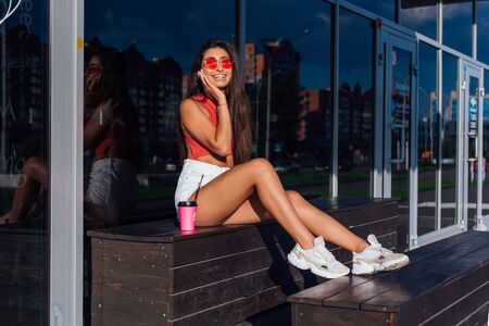 Stylish happy young woman wearing white shorts and sneakers holding pink cup of coffee to go sitting next to coffee shop. Portrait of smiling girl sitting on the bench with coffee. Фото со стока
