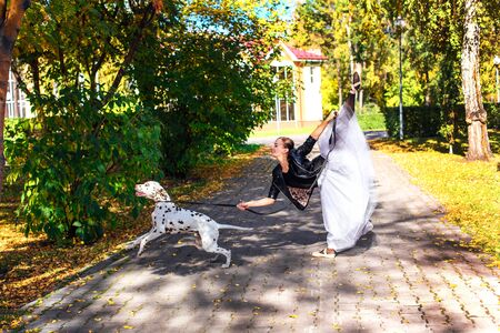 Ballerina with Dalmatian dog in the golden autumn park. Woman ballerina in a white ballet skirt and black leather jacket dancing in pointe shoes in autumn park with her spotty dalmatian dog. Stock Photo