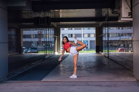 Young beautiful brunette woman dancing in mirror arch of building. Stockfoto