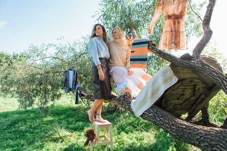 Portrait of two beautiful women brunette and blond sitting on the big brunch of tree in a field in late summer. Concept of harmony, nature, naturalness, fashion, style, friendship