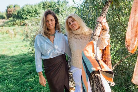 Portrait of two beautiful women brunette and blond standing on the big brunch of tree in a rays of light in a field in late summer. Concept of harmony, nature, naturalness, fashion, style, friendship