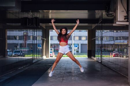 Young beautiful brunette woman jumping in mirror arch of building.