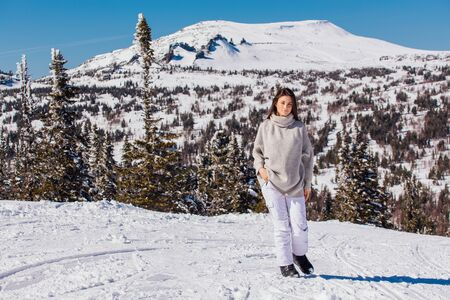 Portrait of a young beautiful brunette woman with blue eyes and freckles on face in winter snowy mountain landscape. Beautiful girl in the winter outdoors dreesed in knitted sweater. Stock Photo