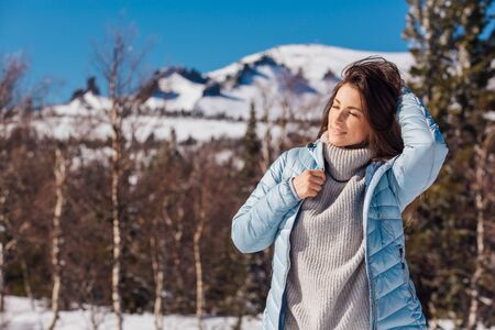 Portrait of a young beautiful brunette woman with blue eyes and freckles on face in winter snowy mountain landscape. Beautiful girl in the winter outdoors dreesed in sweater and blue jacket.
