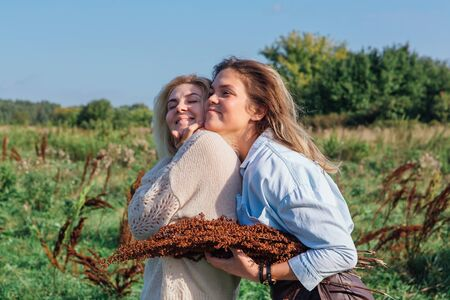 Portrait of two beautiful girls in a field in late summer. Women huging each other with bouquet made of dry brown plants. Concept of harmony, nature, naturalness, fashion, style, friendship
