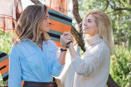 Portrait of two beautiful women brunette and blond holding their hands with same bracelets next to the tree in late summer. Concept of harmony, nature, naturalness, fashion, style, friendship