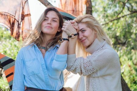 Portrait of two beautiful women brunette and blond holding their hands with same bracelets next to the tree in late summer. Beautiful girls standing next to each other.