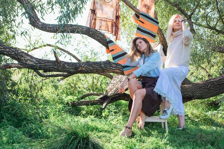 Portrait of two beautiful women brunette and blond sitting on the big brunch of tree in a field in late summer. Beautiful girls standing next to each other. 写真素材