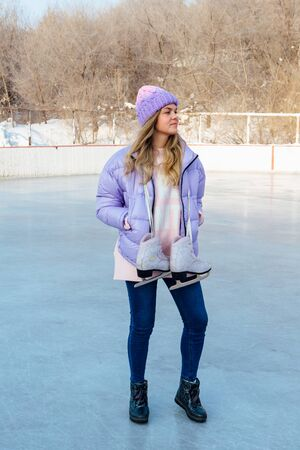 Lovely young woman with ice skates hanging on neck on the ice rink.