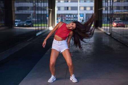 Young brunette woman dancing and shaking her hair in arch of building.