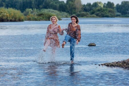 Two pretty sisters standing in river next to the shore on a cloudy windy summer day, having fun, splashing water and laughing. Imagens