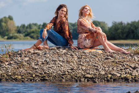 Two pretty sisters sitting on the small stone river island on a cloudy windy summer day, discuss girls secrets, laugh. Imagens